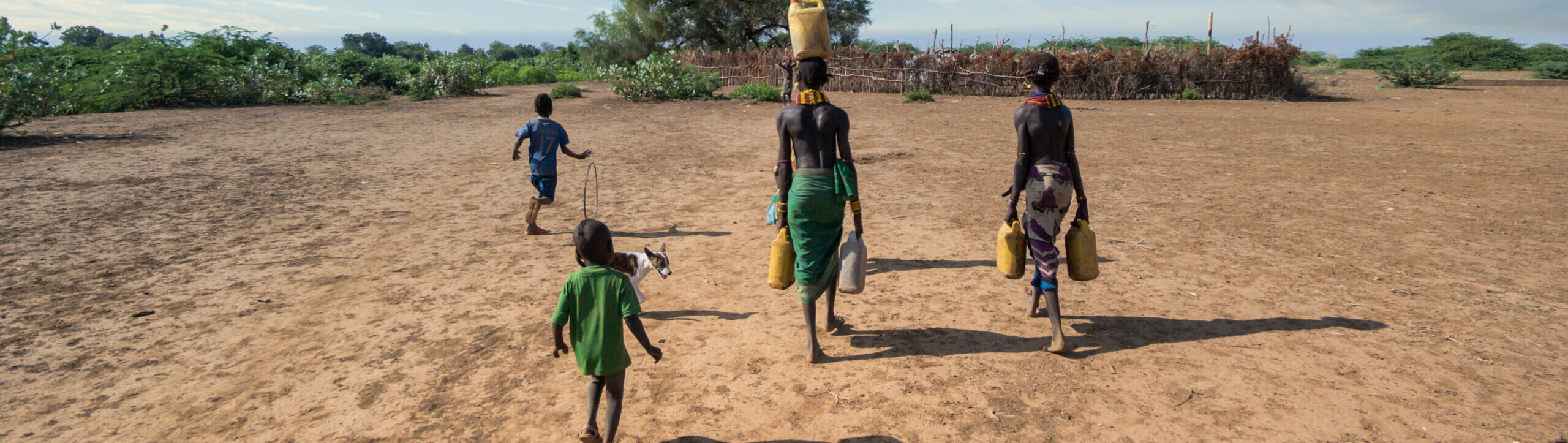 Photo of a four people in African attire carrying water jugs on top of their heads, walking across a dry dirt field. Their backs are to the camera.