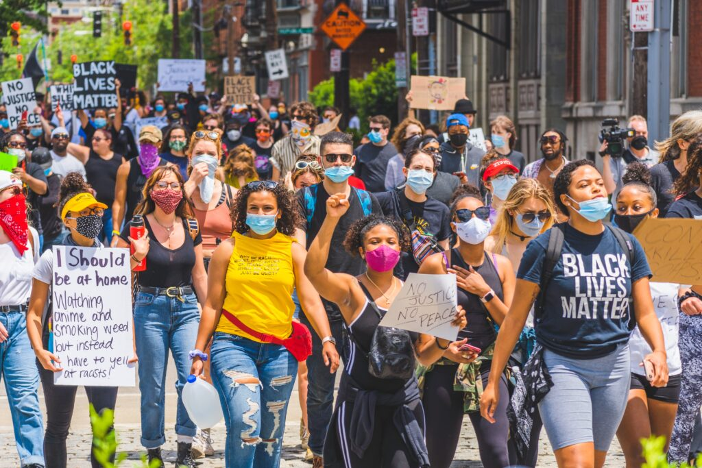 A crowd of protestors holding signs and wearing face masks march the streets in Cincinnati during a #BlackLivesMatter protest, photo by Julian Wan via Unsplash