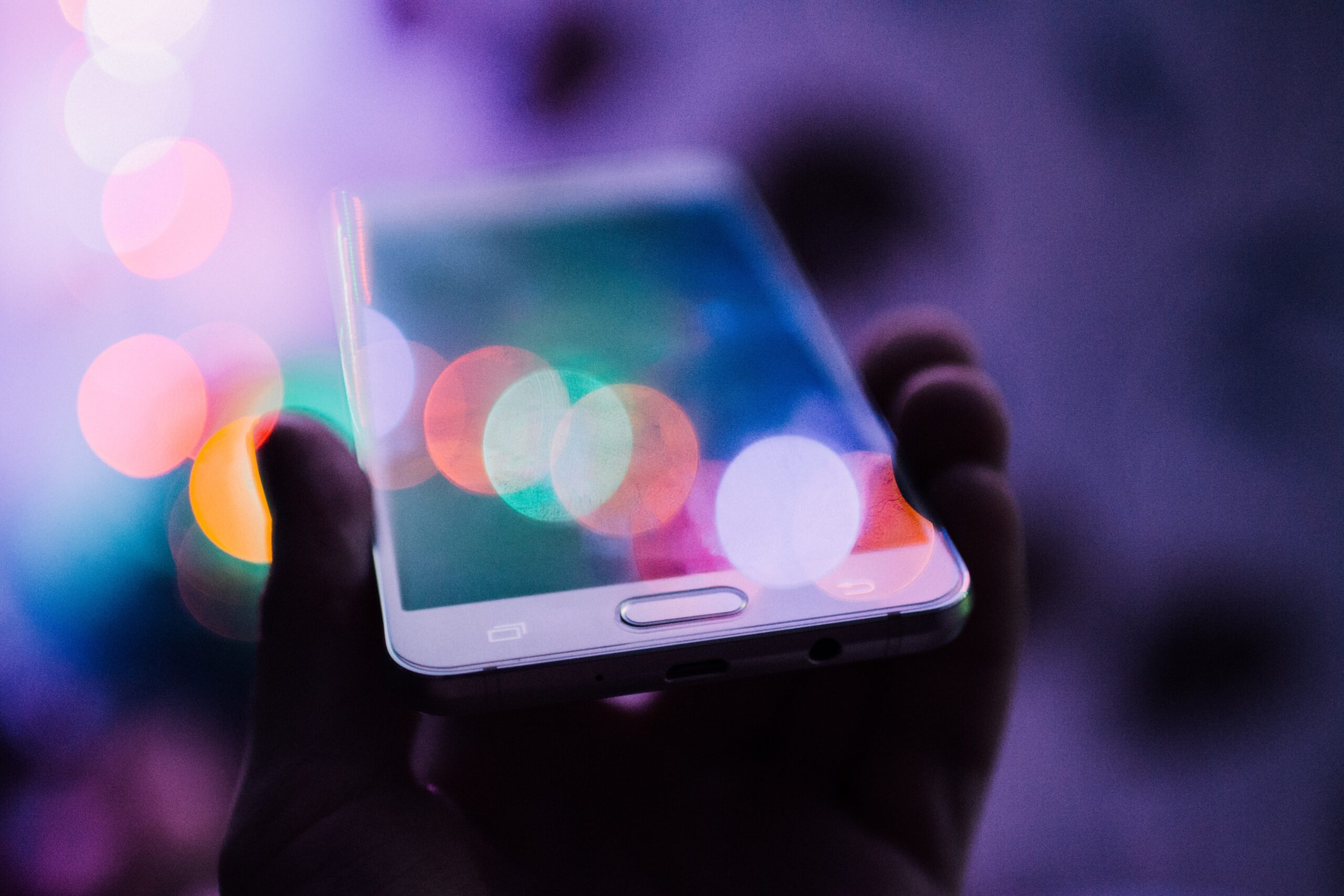A silhouetted hand holding a mobile smart phone with colorful abstract lights surrounding it